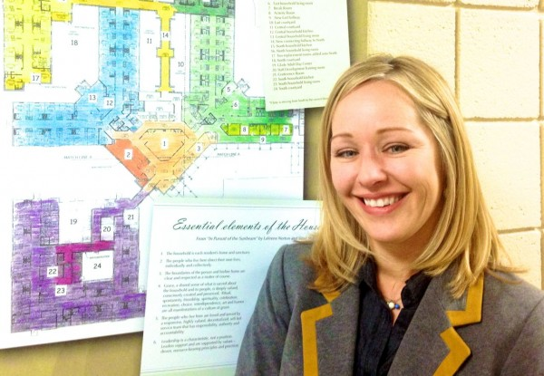Laura Lowe, marketing director stands beside plans for the latest renovations in the assisted living areas.