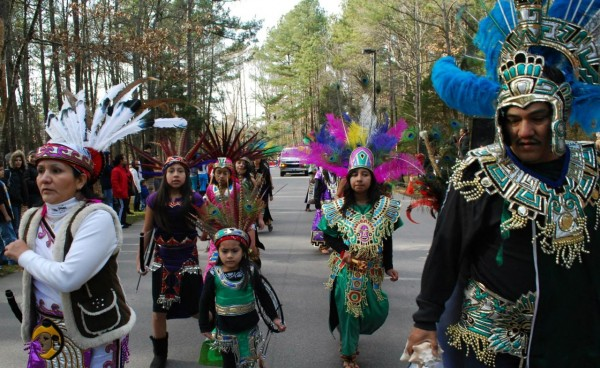 Groups march wearing traditional costumes from their countries