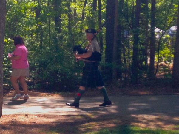 Bagpiper leading a march through the park