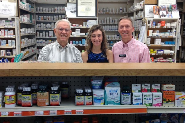 Ralph Ashworth, Cori, and Paul Ashworth stand behind the pharmacy counter at the drugstore