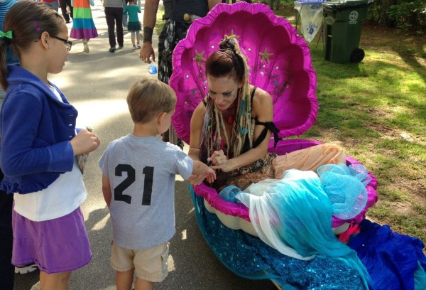 the mobile mermaid was wheeled around the festival where she painted designs on children