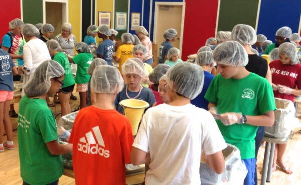 Campers at the Clubhouse @ Bright Horizons package meals for Stop Hunger Now