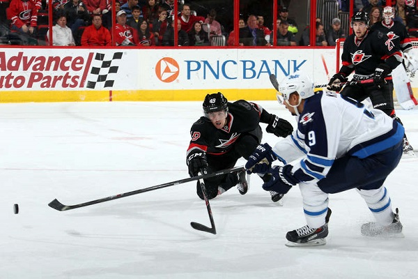 Rask of the Carolina Hurricanes attemps to stick check Kane of the Winnipeg Jets as he tries to control a loose puck.