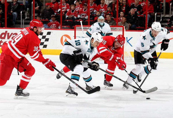 Jiri Tlusty and Patrick Dwyer of the Carolina Hurricanes battle for the puck against Andrew Desjardins and Jason Demers #5 of the San Jose Sharks