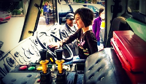 Children are invited to touch, explore, and climb in the trucks.