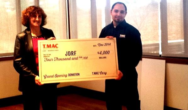 Nathan presents a check to Kathy Peterson, Executive Director at JDRF.