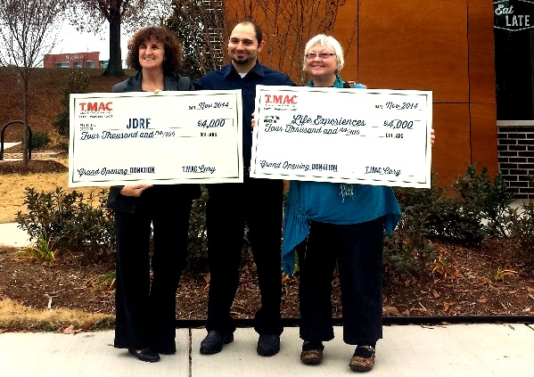 General Manager Nathan Wachob presents checks to two charities outside of the Cary T.MAC