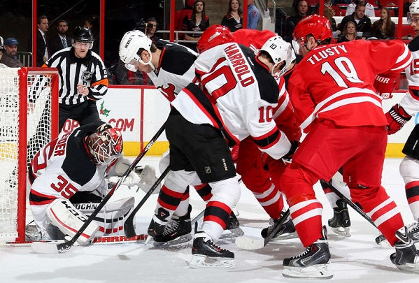 Cory Schneider of the Devils makes a save through traffic in front of the net.