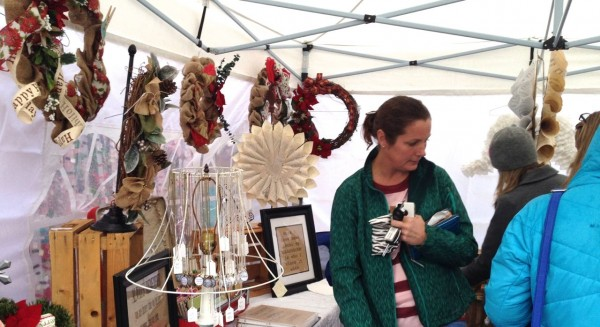 shopper visiting a tent selling wreaths at Ole Time Winter Festival