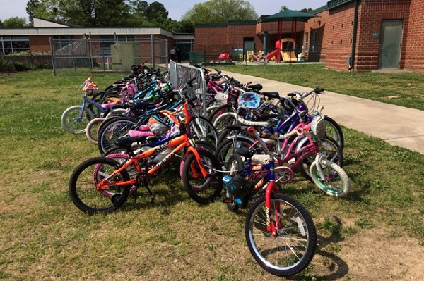 Many elementary students ride their bikes to school. They all have to roll them up the steep, grassy hill beside the staircase.