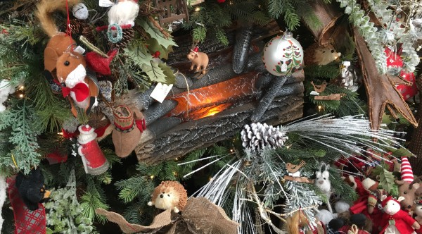 Warm and cozy critters made of felt gather in a tree that includes an electric fireplace.